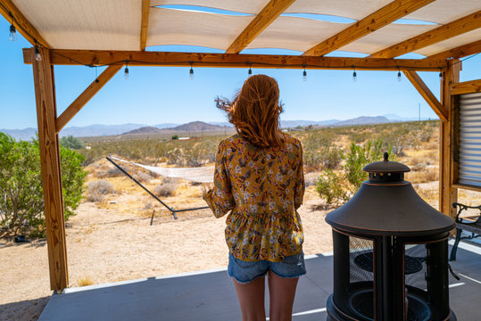 A woman in her twenties in a vintage shirt on a porch in the desert cabana