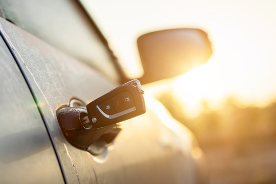 Car keys were plugged into the silver car door at outdoor parking lot with sunlight effect in morning or sunset time