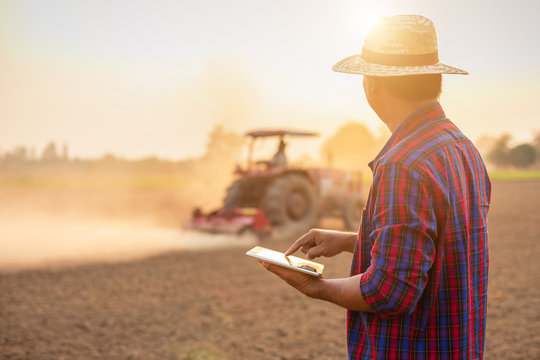 Asian young farmer working and holding tablet in the empty land. Prepare the soil and planning to planting concept