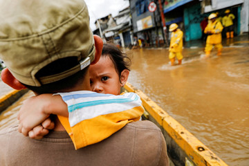 A girl is carried by her father across floodwaters in the Jatinegara area after heavy rains in Jakarta