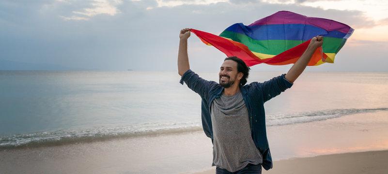 Cheerful guy with a rainbow flag on the beach. Young man holding a rainbow flag against the ocean sky