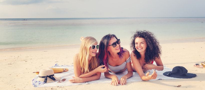 Three beautiful young European slender girlfriends in bright red and striped bikinis lie on the sand at tropical beach on vacation, happiness joy summer and fun