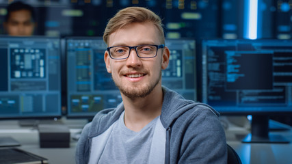Portrait of a Smart and Handsome IT Specialist Wearing Glasses Smiles, Behind Him Personal Computers with Screens Showing Software Program with Coding Language Interface in Data Center