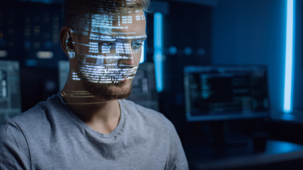 Handsome Young Software Developer Working on Personal Computer in Digital Identity Cyber Security Data Center, Program Coding Language Reflects on His Face. Futuristic Hacking and Programming Concept