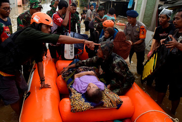 An elderly woman is being evacuated on an inflatable boat by a rescue team, after floods hit a residential area in Bekasi