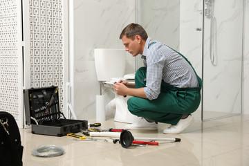Professional plumber repairing toilet bowl in bathroom