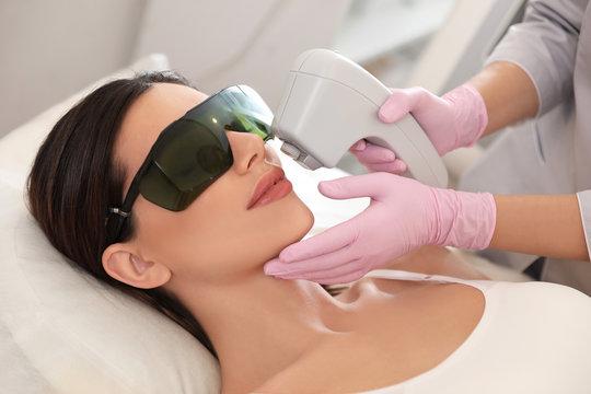Young woman undergoing laser epilation procedure in beauty salon