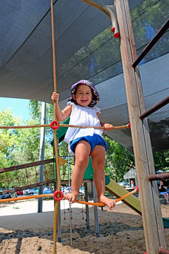 A happy laughing baby girl playing at a playground
