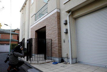 A photographer takes a picture of an exterior of the Tokyo residence of former Nissan chairman Carlos Ghosn, while prosecutors raid the house, in Tokyo