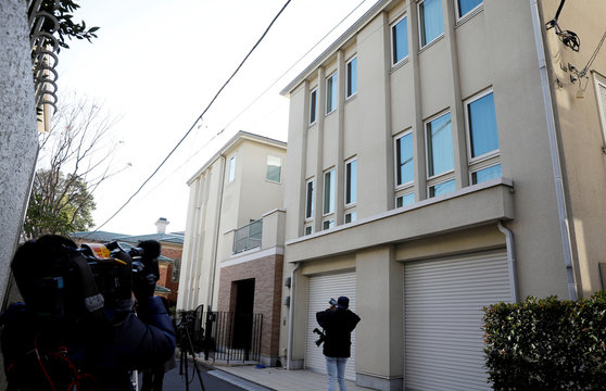 A TV cameraman films exterior of the Tokyo residence of former Nissan chairman Carlos Ghosn while prosecutors raid the house in Tokyo