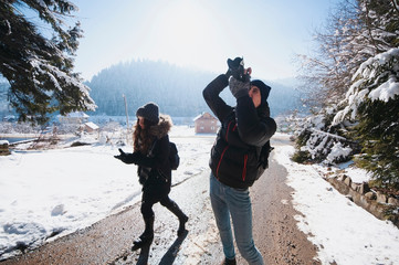 Young hiker backpacker taking photo in the winter forest,Ukrainian Carpathian Mountains