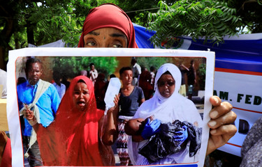 Somali women hold a photograph of a child injured at the car bomb explosion at the Afgoye junction, as they participate in a protest against al-Shabaab militia outside the General Kahiye Police Academy in Mogadishu