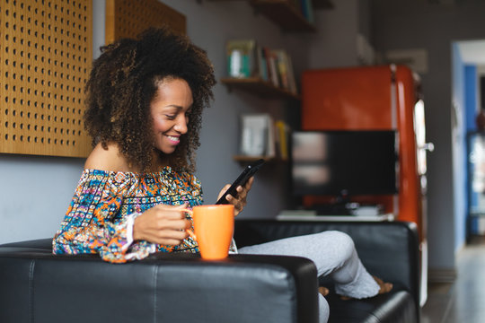 Casual young black woman relaxing at home texting on smartphone and drinking coffeee. Home leisure and tranquility concept. Afro hairstyle model.