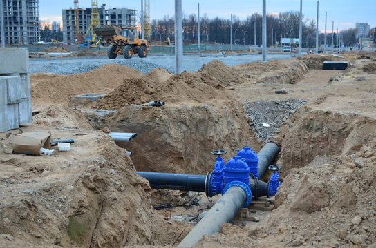 Construction of main water supply pipeline. Laying underground storm sewers at construction site, water main, sanitary sewer, drain systems. Installation of the gate valves for city groundwater system