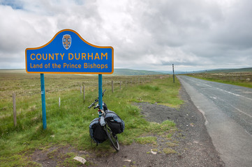 A touring bike leaning against a sign post on the border of County Durham, northern England