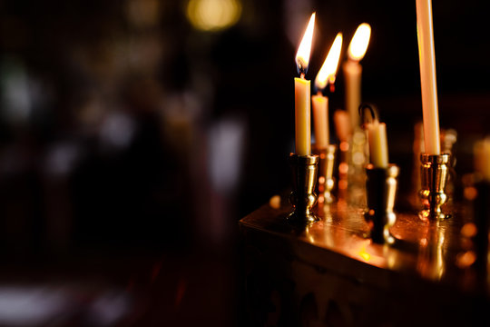 burning candles in church on dark background