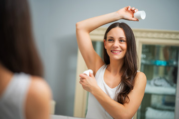 Portrait of young woman who is applying roller deodorant in her armpit.