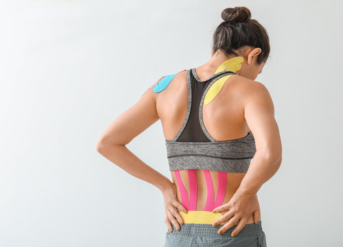 Sporty woman with physio tape applied on back against light background