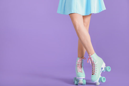 Legs of young woman on roller skates against color background