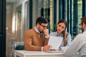 Worried couple looking at paper document in the office of financial adviser.