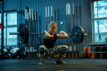Caucasian teenage girl practicing in weightlifting in gym. Female sportive model training with barbell, looks concentrated and confident. Body building, healthy lifestyle, movement and action concept.