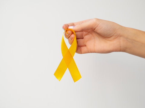 Gold ribbon hanging on fingers on white background. International Childhood Cancer Day concept