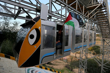A man holding a Palestinian flag enjoys a ride in an amusement park suspension railway in the southern Gaza Strip