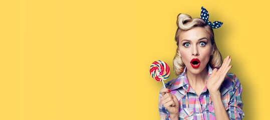 Excited surprised woman with candy lollipop. Girl pin up, gesturing. Retro fashion and vintage concept. Yellow color background. Copy space for some advertise slogan or text.
