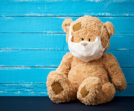 big teddy bear are sitting in white medical masks on a blue wooden background
