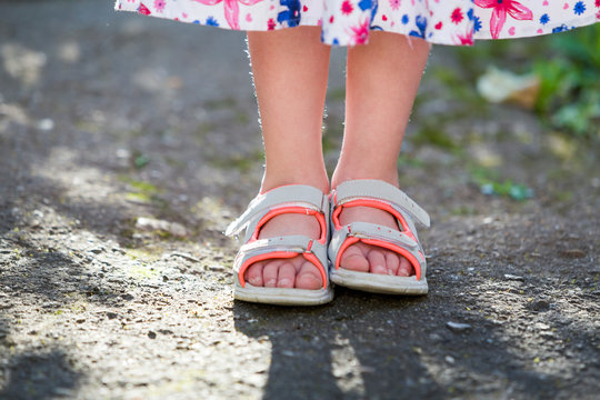 Close up of child girl feet wearing summer sandals shoes