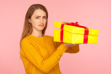 Portrait of unhappy red hair girl in sweater opening gift box and looking sadly at camera,...
