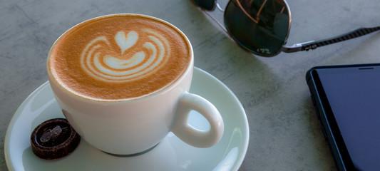 Apetitoso café servido en una taza blanca, con y una bella imagen dibujada en la superficie
