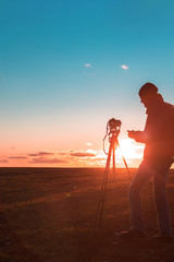 Canvas Prints Magenta photographer with a tripod and camera takes a landscape during sunset in a large open area