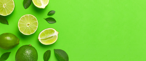 Fresh juicy lime and green leaves on bright green background. Top view flat lay copy space. Creative food background, tropical fruit, vitamin C, citrus. Composition with whole and slices of lime