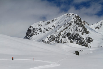 Snowshoer on sunny snowy mountain, Minschuns, Canton of Grisons, Switzerland