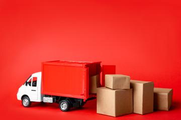Toy truck with boxes on red background Logistics and wholesale concept