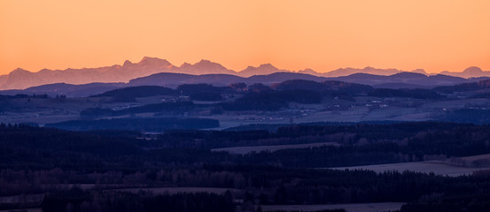 sunrise in mountains - landscape with mountains on horizon, clean yellow and orange sky