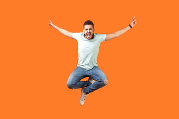 Full length of crazy overjoyed brunette man in white outfit jumping in air with raised hands, screaming loud for joy, feeling energetic and lively. indoor studio shot isolated on orange background