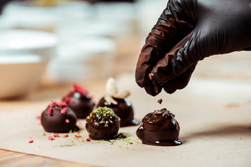 cropped view of chocolatier in black latex glove adding chocolate shavings on fresh made candies
