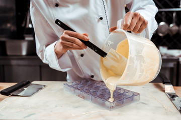 cropped view of chocolatier pouring melted white chocolate into ice tray