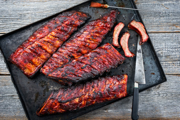 Barbecue pork spare ribs St Louis cut with hot honey chili marinade as top view on an old rustic...