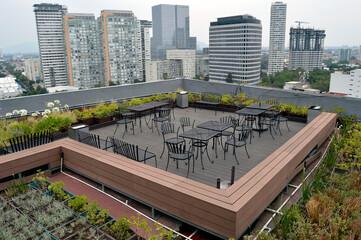 azotea verde con mesas y sillas en la ciudad