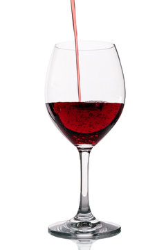 Red wine pouring into clean glass on white background with bubbles. Tasty wine being poured in wine glass. Studio shot