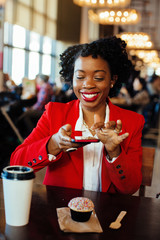 Portrait of a smiling woman sitting in a cafe taking a cell phone picture of her cupcake