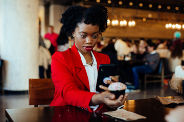 Portrait of a young woman sitting in a cafe taking a cell phone picture of her cupcake