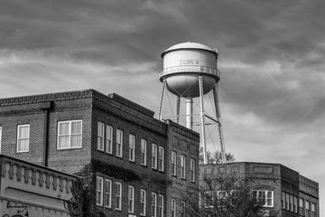 Water tower over brick buildings in monochrome
