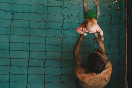 High angle view of father with baby in swimming pool