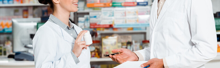 Cropped view of pharmacists with clipboard and pills in drugstore