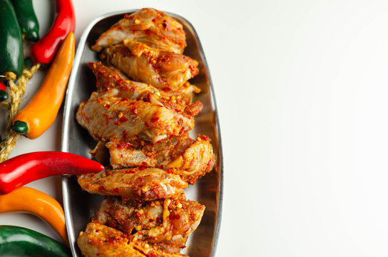 Raw and fresh chicken wings in a siriracha marinade
