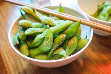 Edamame beans in Japanese restaurant in bowl with chopsticks